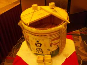 A drum-shaped sake container, with dipping cups