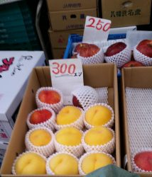 Since a yen is very close to a penny, the peaches are $3.00 each, and the apples only $2.50.